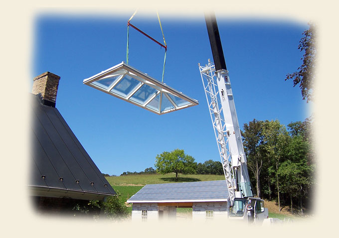 A Hipped White Aluminum Metal Clad Skylight Being Crane-Hoisted by Renaissance Conservatories